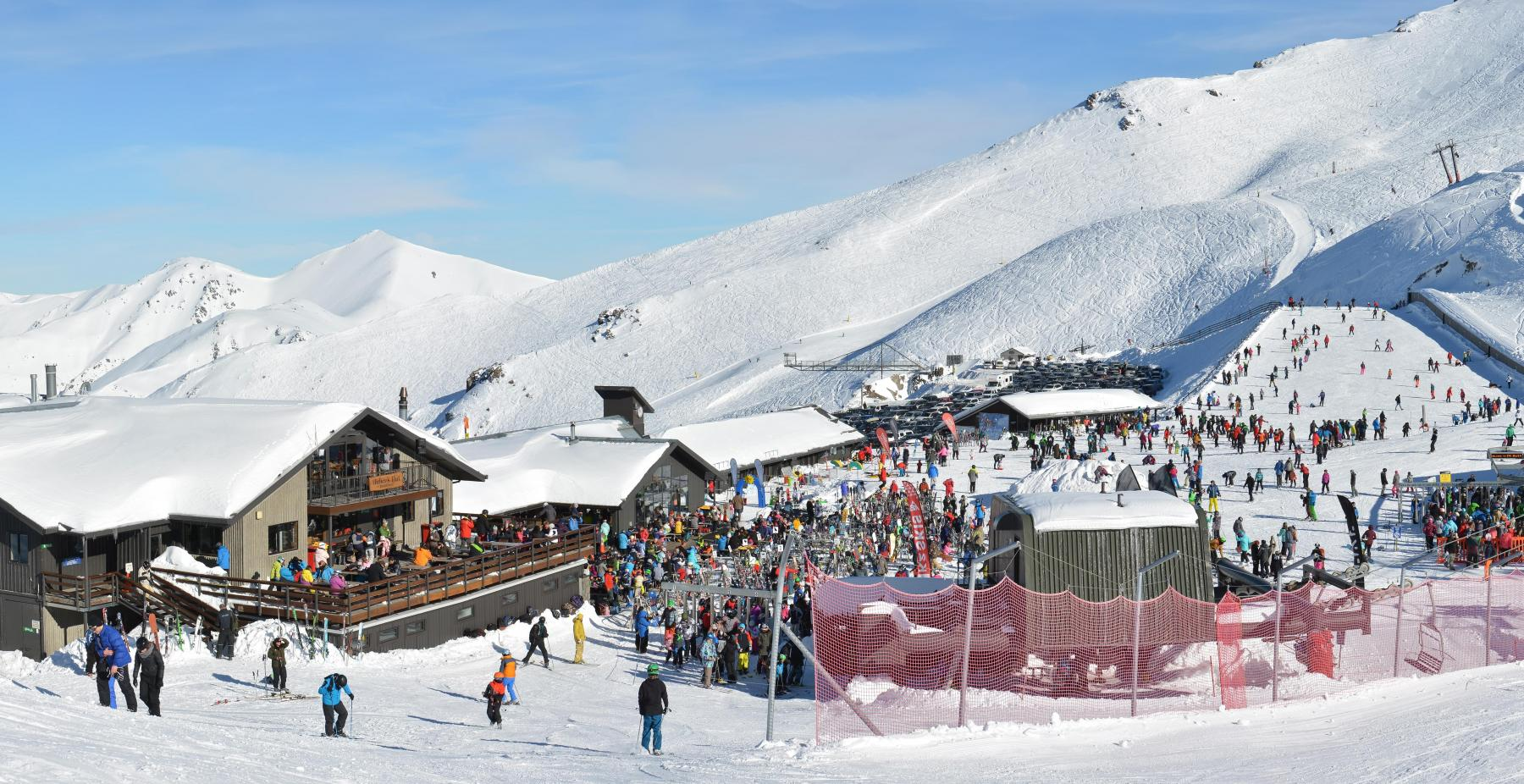 Panoramic view of the Mount Hutt Ski Field at Lunch Time. Skiers prepare to ride on the Chairlift outside the restaurant, Canterbury New Zealand_Shutterstock-min
